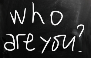 """""""Who are you"""" handwritten with white chalk on a blackboard"""